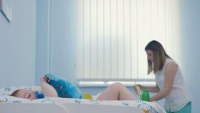 La madre prepara la miscela in bottiglia sulle sfuocature fondo ed il ragazzino mette sul pannolino video d archivio