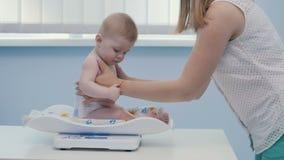La madre puso al bebé en el pesador en gabinete del ` s del doctor metrajes