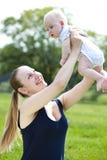 La madre que cuida está celebrando al bebé, contra parque del verano Foto de archivo libre de regalías