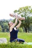 La madre que cuida está celebrando al bebé, contra parque del verano Imágenes de archivo libres de regalías