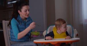 La madre que intenta alimentar su niño y lo no quiere comer las gachas de avena y el griterío almacen de video