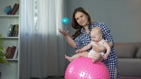 La madre responsable que hace el desarrollo temprano ejercita con el bebé activo almacen de metraje de vídeo