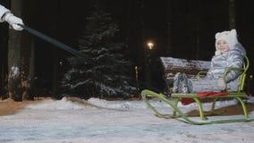 La madre rotola una piccola figlia su una slitta nel parco dell'inverno di sera archivi video