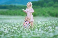 La madre rubia con rosa colorido blanco que lleva de la pequeña hija linda se viste en el campo de la manzanilla, tiempo de veran Fotografía de archivo