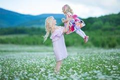 La madre rubia con rosa colorido blanco que lleva de la pequeña hija linda se viste en el campo de la manzanilla, tiempo de veran Foto de archivo libre de regalías