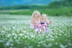 La madre rubia con rosa colorido blanco que lleva de la pequeña hija linda se viste en el campo de la manzanilla, tiempo de veran Imagen de archivo libre de regalías
