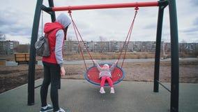 La madre sacude a su niño en el oscilación en parque en día nublado almacen de metraje de vídeo