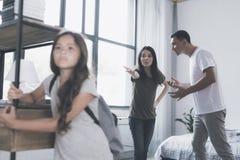 La madre señala airadamente su mano del ` s del padre en su hija, que se coloca delante de ellos con una mochila Imagen de archivo libre de regalías