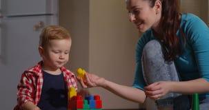 La madre se divierte con el niño que juega aprendiendo los juegos para los niños almacen de video
