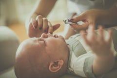 La madre sfrega i denti del suo piccolo neonato Immagine Stock