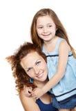 La madre sonriente celebra a la hija en brazos Imagenes de archivo