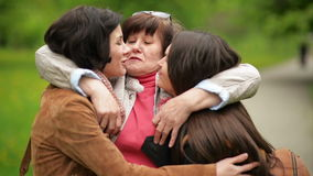 La madre sonriente está abrazando a sus dos hijas adultas al aire libre Tres mujeres hermosas son felices juntas almacen de metraje de vídeo
