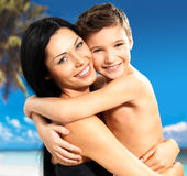 La madre sonriente feliz abraza al hijo en la playa tropical Fotos de archivo