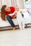 La madre sonriente que ayuda al bebé alegre aprende recorrer Fotos de archivo