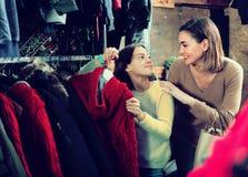 La madre sorridente con la figlia sta comprando il maglione caldo Immagine Stock