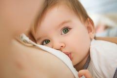 La madre sta allattando al seno il suo bambino a casa Bambino di allattamento al seno della madre in lei armi a casa immagini stock libere da diritti