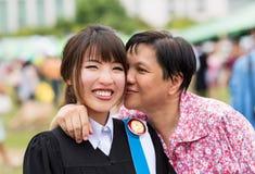 La madre sta baciando sua figlia con la gioia per la sua laurea Immagine Stock