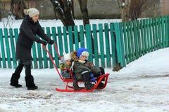 La madre sta conducendo una slitta con due bambini in un villaggio nevoso Immagine Stock Libera da Diritti