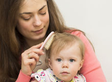 La madre sta insegnando alla figlia a spazzolare i capelli. Fotografia Stock