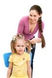 La madre sta pettinando una piccola figlia Immagini Stock