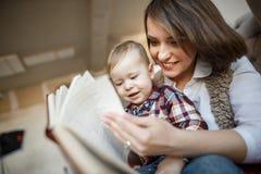 La madre sta sedendosi con il suo bambino e sta leggendo un libro È sorridente ed esaminante lo fotografie stock