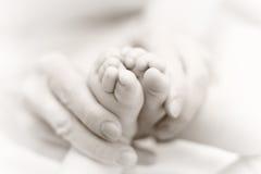 La madre suavemente celebra la pierna del bebé disponible Imagenes de archivo