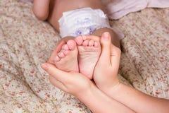 La madre suavemente celebra la pierna del bebé disponible Imagen hermosa del color con el foco suave en pie del bebé imagen de archivo