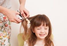 La madre taglia i capelli del ` s della figlia a casa Immagini Stock Libere da Diritti