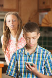 La madre tenta di dare una occhiata a mentre il figlio teenager controlla il suo telefono cellulare Fotografie Stock