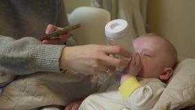 La madre tiene il bambino delle alimentazioni del telefono video d archivio