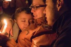 La madre tiene il bambino e la candela addormentati per Festival de Luzes Fe Immagine Stock