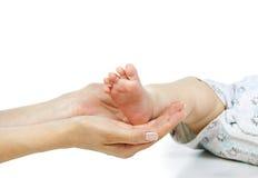 La madre tiene il piedino del bambino Fotografia Stock Libera da Diritti