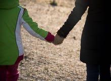 La madre tiene la mano di sua figlia Fotografia Stock