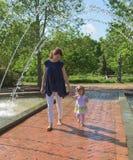 La madre tiene la sua mano del ` s della figlia tramite una fontana in un parco all'aperto fotografie stock