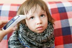 La madre toma la temperatura para su niño con el termómetro infrarrojo Foto de archivo libre de regalías