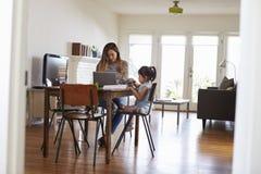 La madre trabaja en el ordenador portátil mientras que la hija dibuja la imagen en libro imagen de archivo