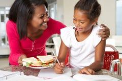 La madre trae el bocadillo de la hija mientras que ella estudia Foto de archivo