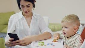 La madre utilizza il telefono durante il piccolo figlio che mangia il biscotto video d archivio
