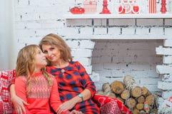 La madre in vestito rosso sorride e tiene un bambino adorabile Fotografie Stock