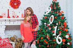 La madre in vestito rosso sorride e tiene un bambino adorabile Fotografia Stock Libera da Diritti
