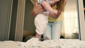La madre viene ad un bambino gridante a cambiare il suo pannolino archivi video