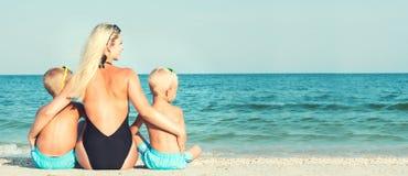 La madre y dos hijos se est?n sentando en la arena y est?n mirando el mar Vacaciones de verano imagenes de archivo