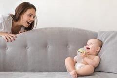 La madre y el bebé están jugando en el sofá fotografía de archivo