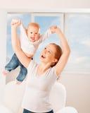 La madre y el bebé están jugando a juegos activos, hacen la gimnasia y el laug Imagen de archivo