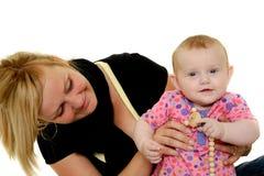 La madre y el bebé están sonriendo Imágenes de archivo libres de regalías