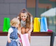 La madre y el bebé examina compras después de hacer compras Fotografía de archivo
