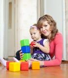 La madre y el bebé juega con los bloques en hogar Imagen de archivo libre de regalías