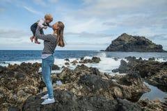 La madre y el bebé juegan cerca de la orilla de mar en Garachico Foto de archivo libre de regalías