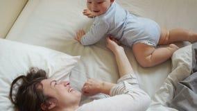La madre y el bebé que cuidan están jugando en cama por la mañana El bebé rueda sobre y los arrastres, madre lo vuelven detrás, b metrajes