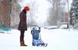 La madre y el bebé recorren en invierno con los trineos Foto de archivo